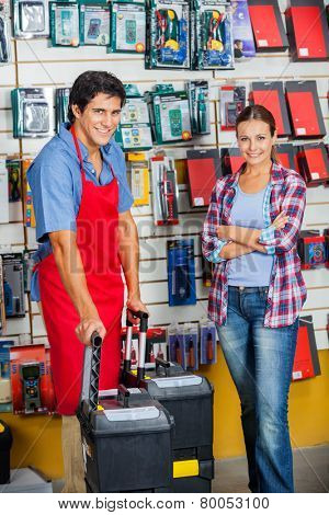 Portrait of confident female customer and salesman with tool cases in hardware store