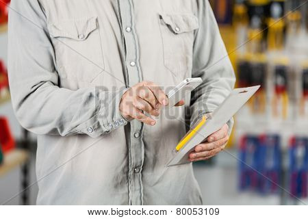 Midsection of male customer scanning tool packet through mobilephone in hardware store