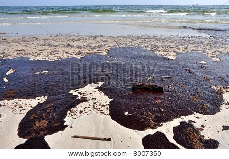 Oil spill on beach with off shore oil rig in background. poster