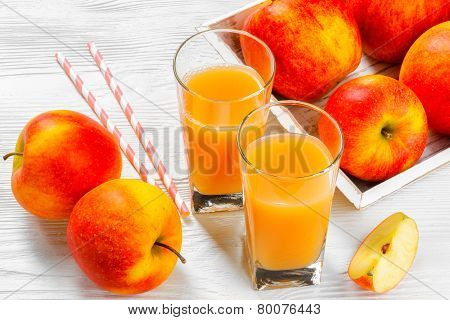Glass of apple juice with apples on white wood background