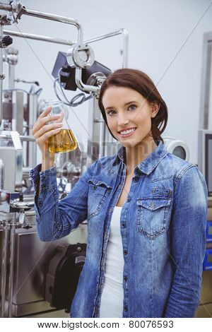 Smiling woman holding a beaker of beer in the factory
