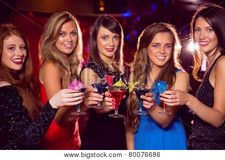 Pretty friends drinking cocktails together at the nightclub