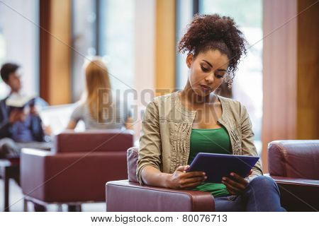 Focused student sitting on sofa using her tablet pc at the univeristy