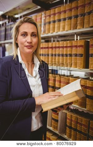 Woman reading a book from shelf standing in library
