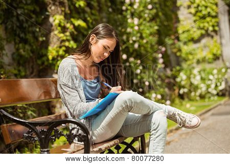 Smiling student sitting on bench and writing on notepad in park at school