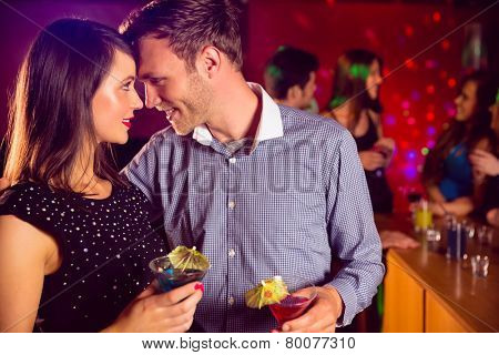 Cute couple drinking cocktails together at the nightclub