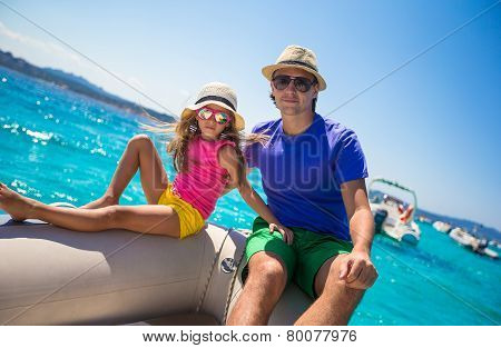 Young father with little girl resting on a big boat