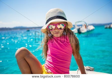 Cute little girl enjoying sailing on boat in the open sea