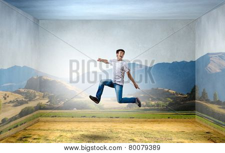 Young man jumping in sky in 3d room