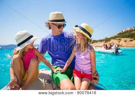 Young father with adorable girls resting on a big boat