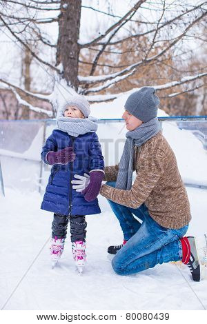 Happy father and little girl vacation on skating rink