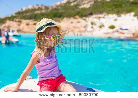 Cute little girl enjoying sailing on boat during summer vacation