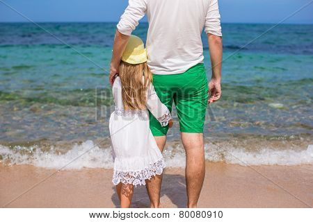 Adorable little girl and happy dad during beach vacation