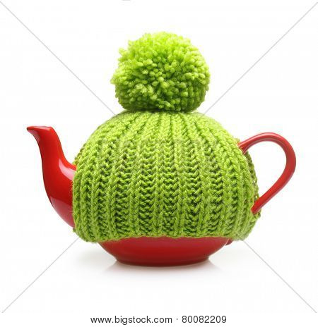 Red teapot in green hat isolated on white background