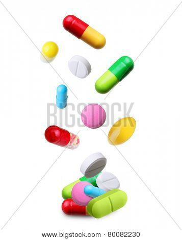 Falling pills isolated on white background.