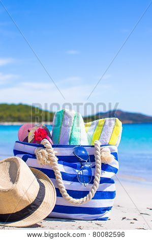 Blue bag, straw hat, flip flops and towel on white beach