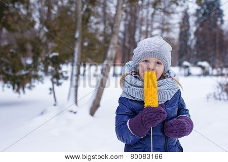 Little girl eating corn outdoor on winter day