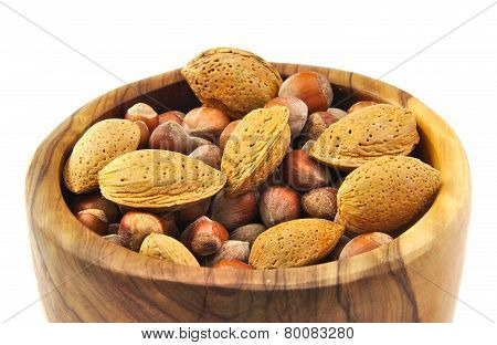 Almonds and nuts in a handmade wooden bowl isolated on white background.