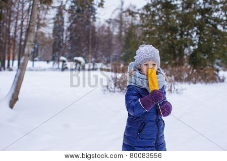 Little girl with sweet corn at winter park
