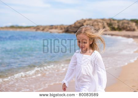 Adorable little girl at tropical beach during vacation