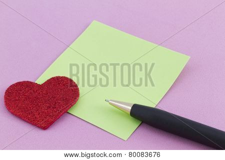 Red Heart, Green Note, And Pen On Pink Background