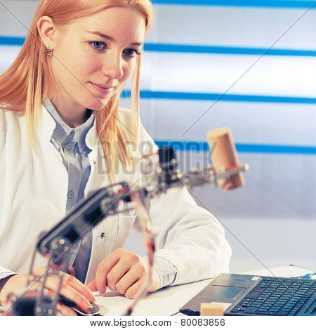 schoolgirl adjusts the robot arm model, girl in a robotics laboratory
