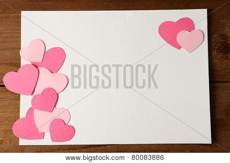 Beautiful hand made post card  with paper hearts on color wooden background