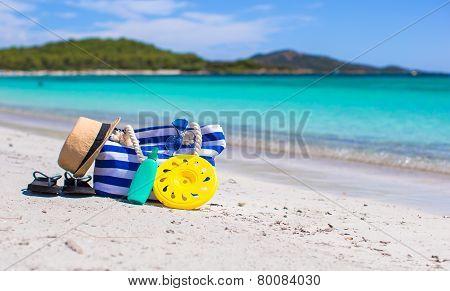 Stripe bag, straw hat, sunblock and towel on beach