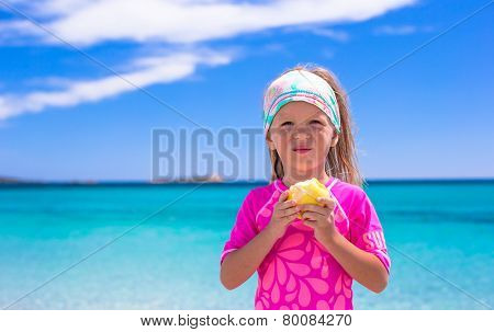 Adorable little girl eat apple at tropical beach during vacation