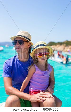 Young father with adorable girl resting on a big boat