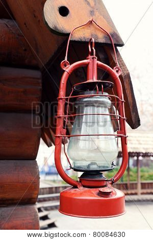 Kerosene lamp hanging on wooden house, outdoors
