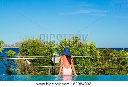 Young woman relaxing near the swimming pool