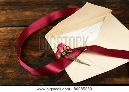 Envelope with love letter, vinous ribbon and dried rose on rustic wooden table background