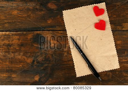 Blank sheet of paper with pen and two hears on rustic wooden table background