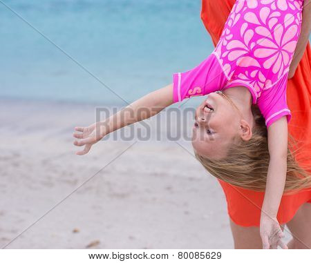 Little happy girl enjoy summer vacation with her mom at exotic beach