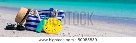 Stripe bag, straw hat, sunblock and towel on beach