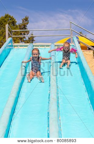Cute girls on water slide at aquapark during summer holiday