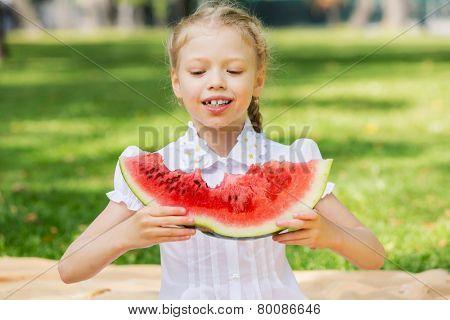 Cute girl in park eating juicy watermelon