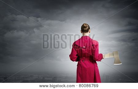 Rear view of woman in red coat with axe in hands