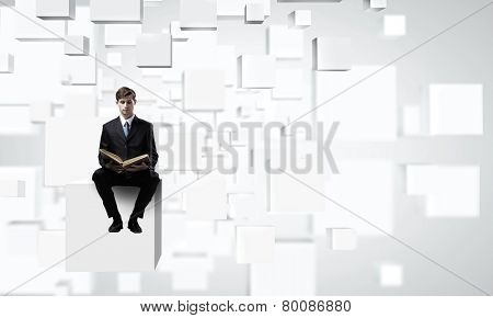 Handsome businessman sitting on white cube and reading book