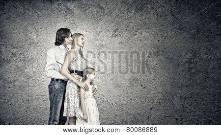 Happy family of mother father and daughter against cement wall