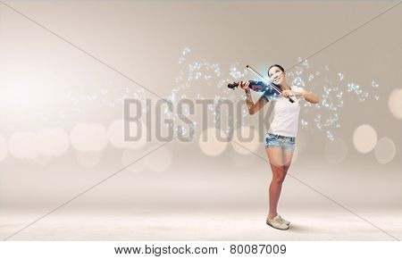Young girl in shorts and shirt playing violin