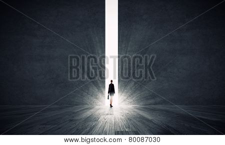 Rear view of businesswoman standing in light of crack in wall