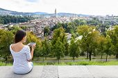 Tourist with smart phone camera in Bern, Switzerland at Rosengarten, the Rose Garden view. Woman taking photograph with smartphone at enjoying view of Berne landmarks and tourist attractions. poster