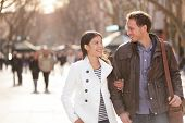 Urban couple walking on La Rambla Barcelona arm in arm. Romantic laughing lovers talking holding hands on date. Young multicultural couple Asian and Caucasian on La Rambla Barcelona, Catalonia, Spain. poster