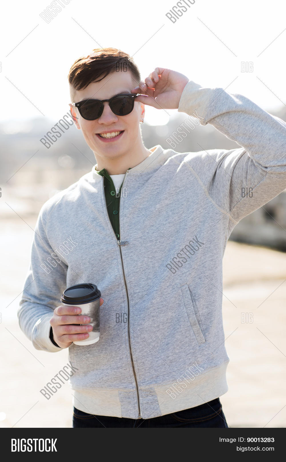 drinks and people concept - smiling young man or teenage boy drinking coffee from paper cup outdoors