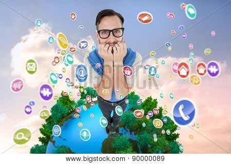 Geeky hipster looking nervously at camera against beautiful blue cloudy sky
