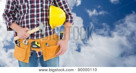 Repairman with hard hat and hammer against bright blue sky with clouds