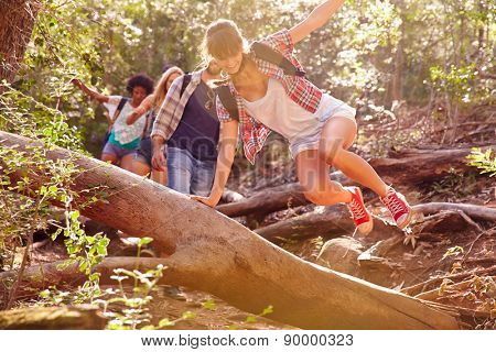 Group Of Friends Jumping Over Tree Trunk On Countryside Walk