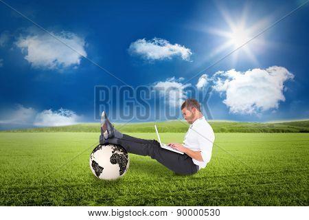 Businessman using tablet against sunny green landscape